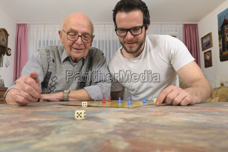 grandfather and grandson playing together ludo