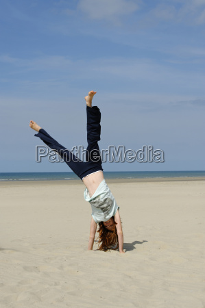 france girl doing handstand at beach