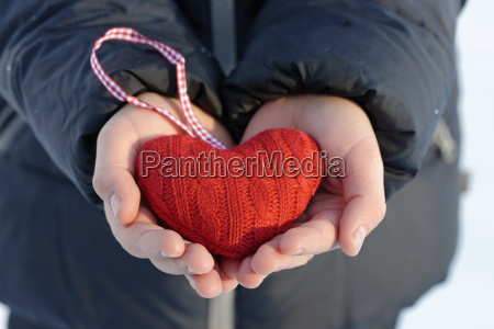hands holding red knitted heart close