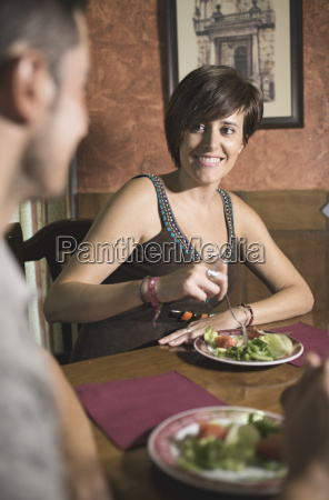 couple eating a salad in restaurant