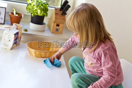 little girl wiping kitchen table