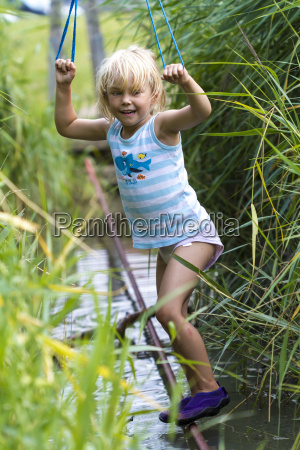 little girl balancing on tightrope at
