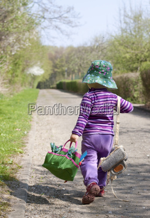 little girl with hat carrying bags