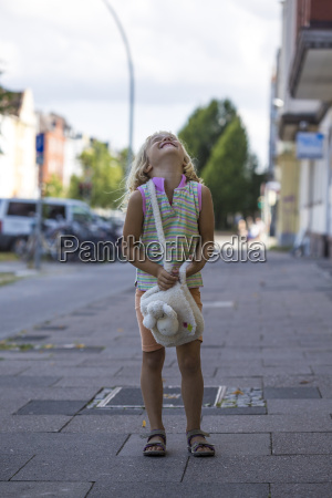 laughing little girl standing on pavement