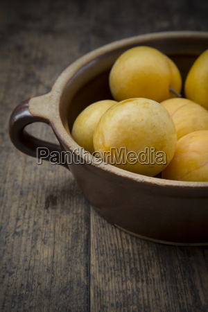 yellow plums in ceramic bowl on