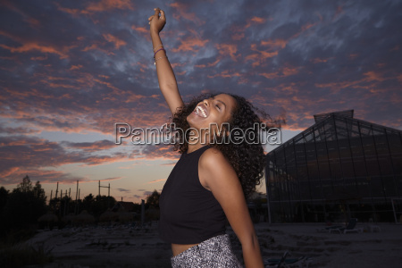 happy young woman dancing at evening