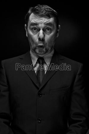 surprised mature man against black background