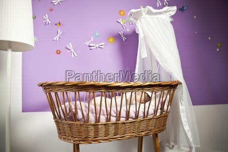 baby girl sleeping in wicker crib