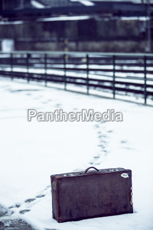 old suitcase standing in snow on