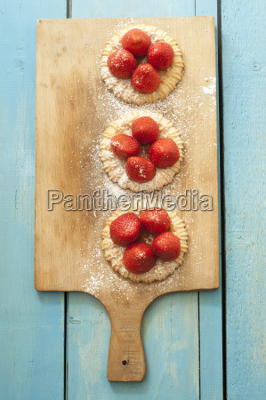strawberry tartlets on chopping board close