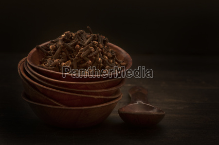 bowl of cloves with wooden spoon