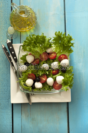 plate of salad with oil bottle