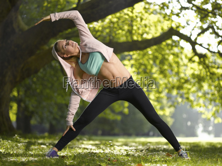 young woman making stretching exercise on