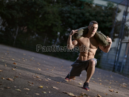 muscly young man training with sandbag