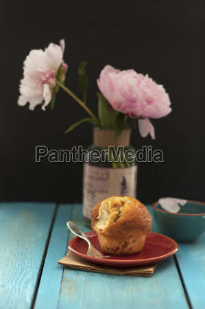 sweet muffin on plate and peonies