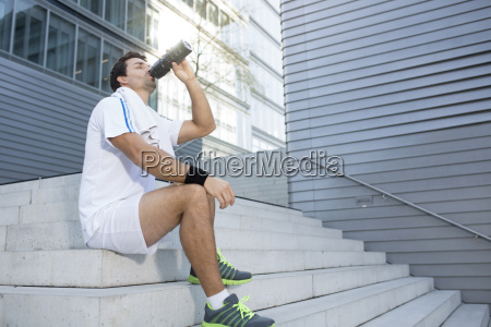 sportsman having a break drinking out