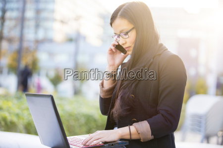 young businesswoman with laptop telephoning with