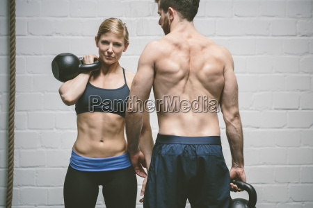 couple in gym training with kettle