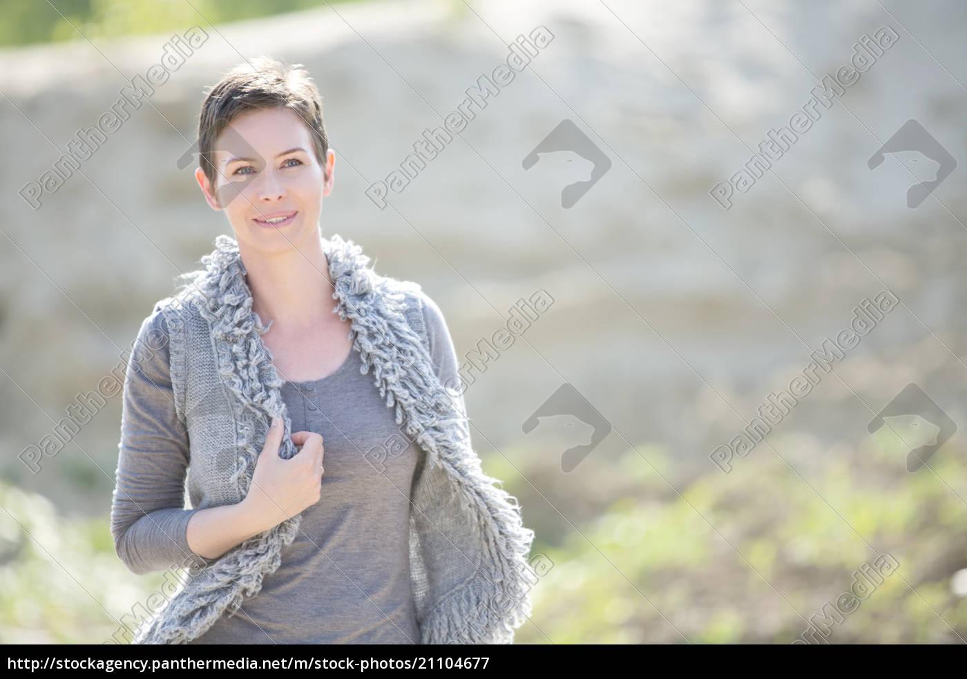 portrait, of, smiling, woman, wearing, grey - 21104677