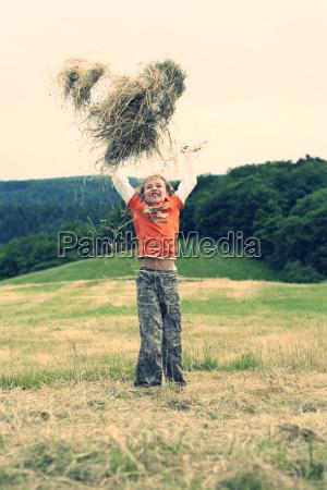 little girl throwing hay