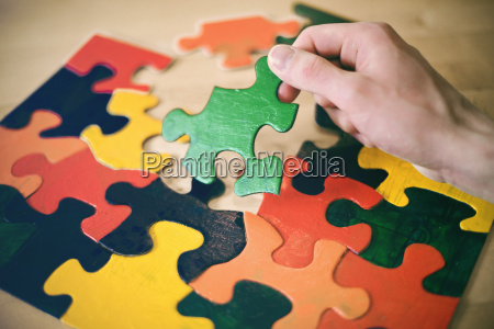 hand holding up a large puzzle