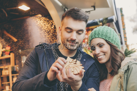 couple looking at handmade wooden decoration