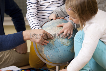 teacher and pupils pointing at globe