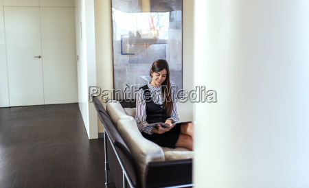 young woman reading magazine at waiting