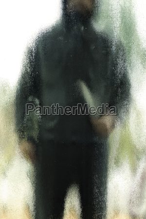 man with knife behind frosted glass