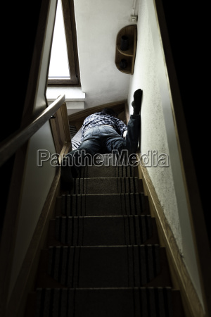 corpse of man lying on staircase