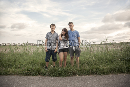 netherlands three smiling teenagers standing in
