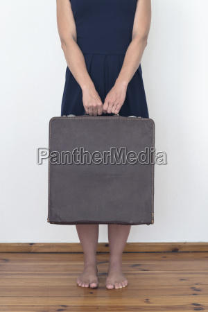 woman standing holding suitcase