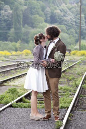 kissing bridal couple standing between rails