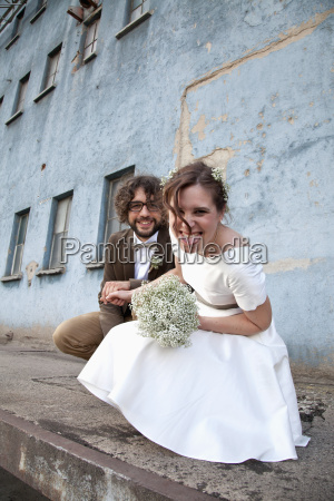 bridal couple crouching in front of