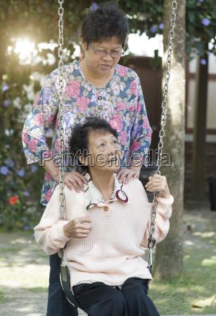 asian elderly women playing swing at