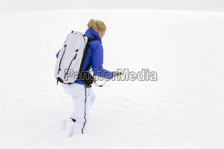 woman prepating for ski tour carrying