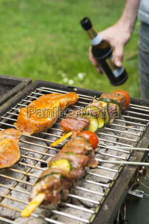 man holding beer bottle at barbecue