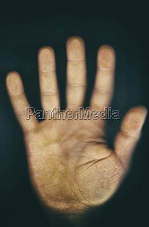 mans hand on glass pane