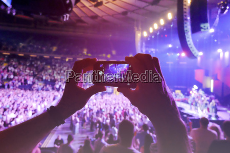 hands holding smart phone filming concert