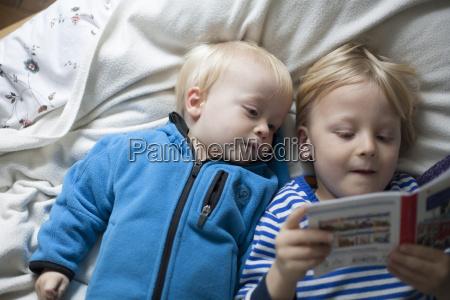 two little boys lying on blanket