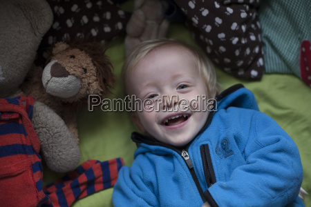 portrait of laughing little boy lying