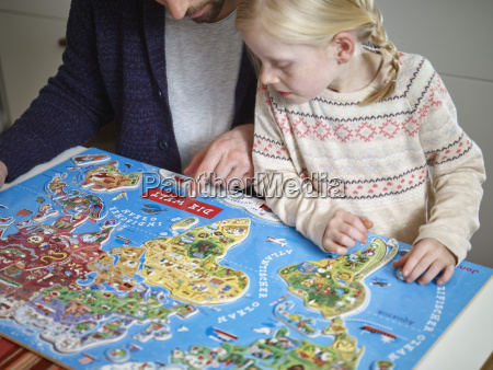 father and daughter playing with world