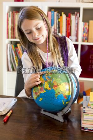 girl pointing at globe