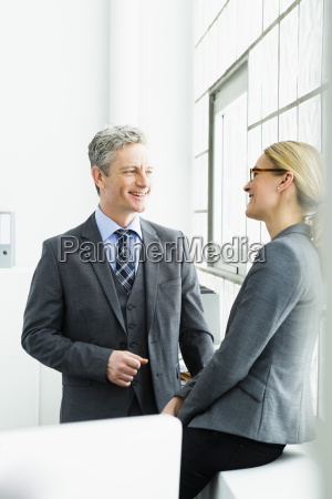 germany businesspeople discussing in office smiling