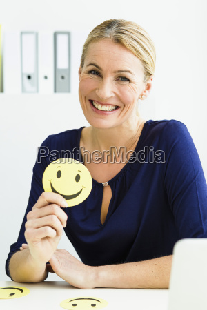 germany portrait of businesswoman holding smiley
