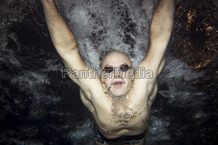 mid adult man diving in butterfly