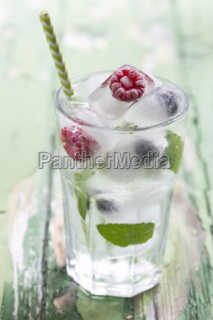 glass of berries in ice cubes