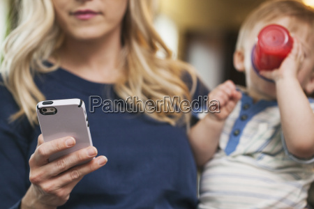 mother checking sms while holding child
