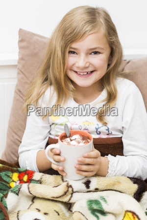 smiling little girl holding cup of