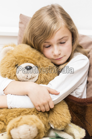 sad little girl cuddling with her